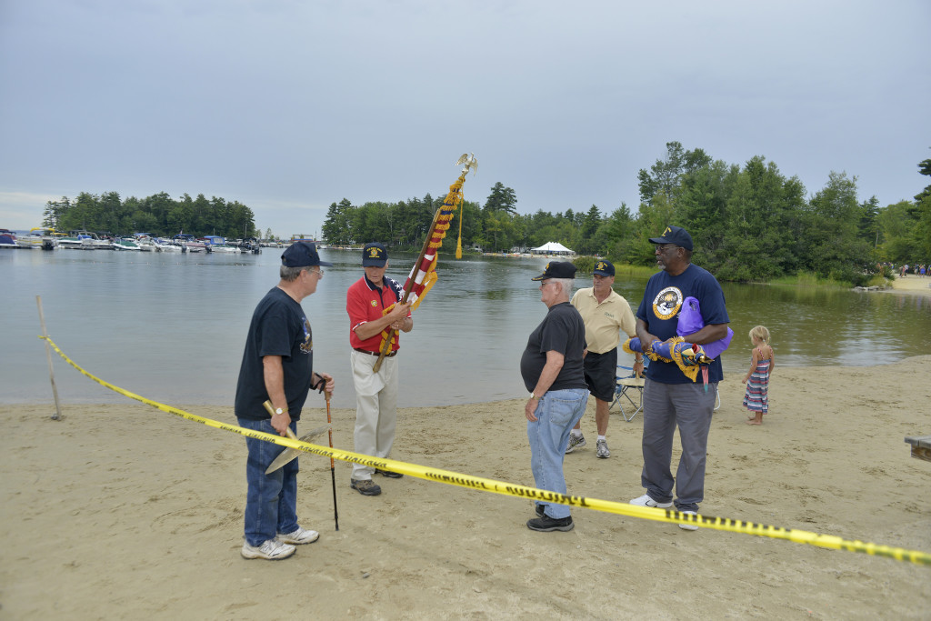 From left, Walter Braley, Bob Akins, Chuck Whynot, Dennis Marshall and Willie Goodman, from VFW 10643 in Windham, take the flags presented during the Navy SEALs fundraising swim on Sebago Lake in Standish on Thursday.