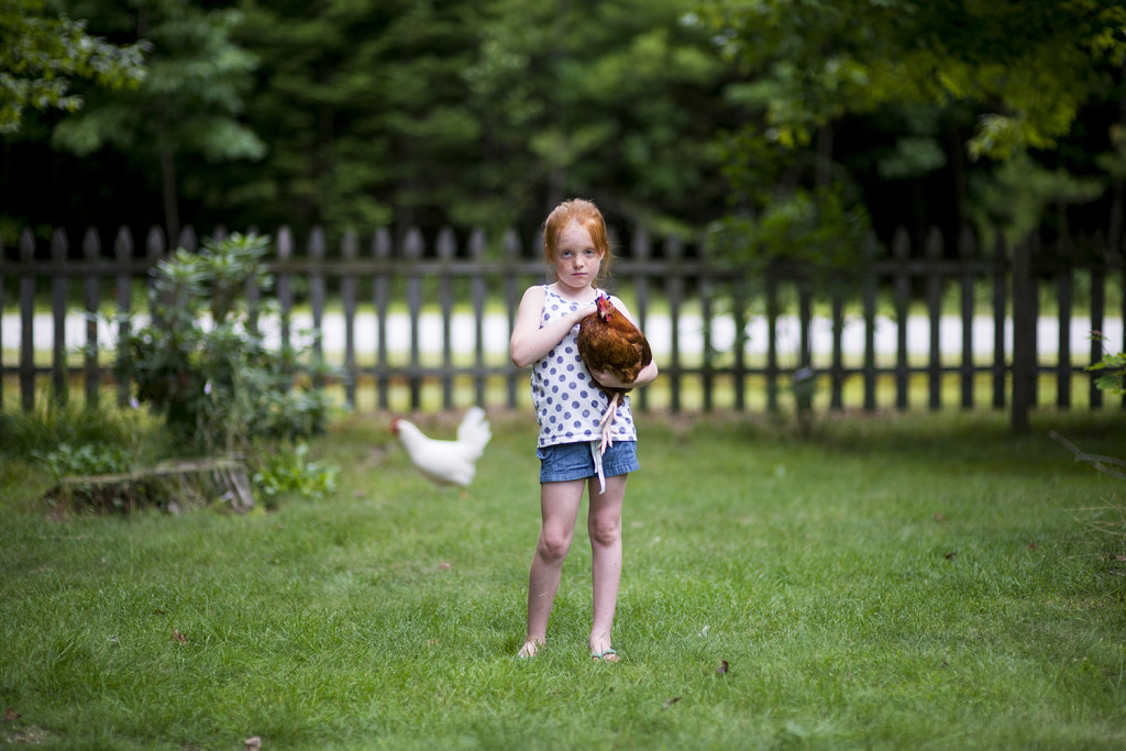 Five-year-old Poppi Gleason poses with her chickens in her front yard in Standish.