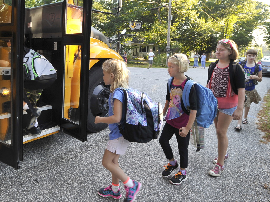 First grade students Elizabeth Baker, Neallie Morey, and Neallie's sister Carly, a fifth-grader, were among RSU 14 students in Windham to board a school bus Tuesday for the first day back to school. John Patriquin/Staff Photographer