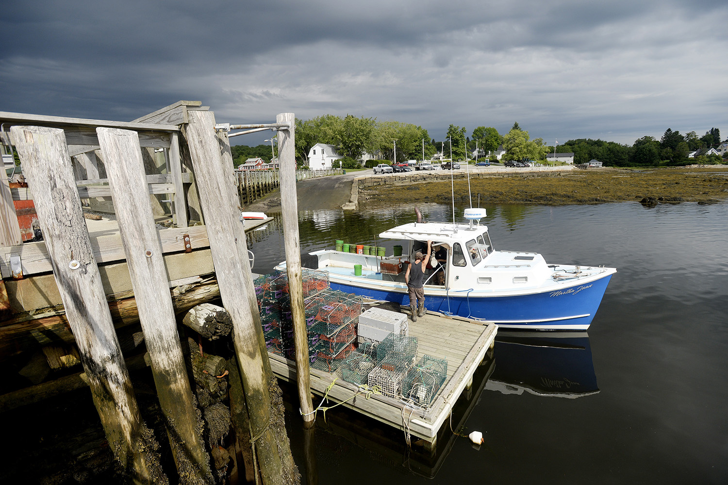 Neil Kirby works on his family's lobster boat as it is docked at the Searsport public landing.