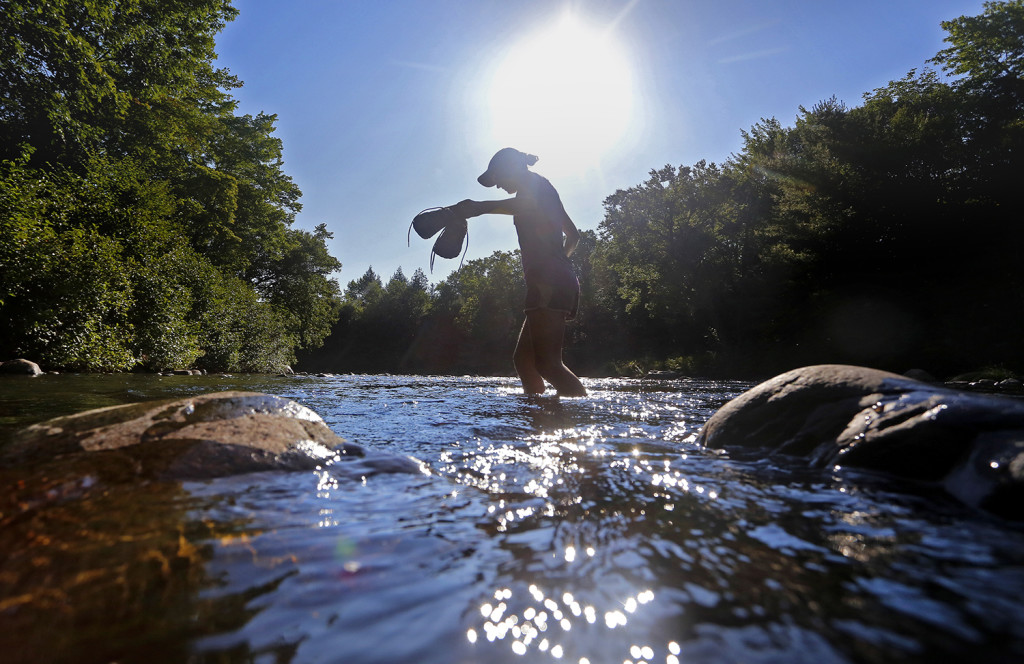 Emily Kallin carries her shoes across a stream.