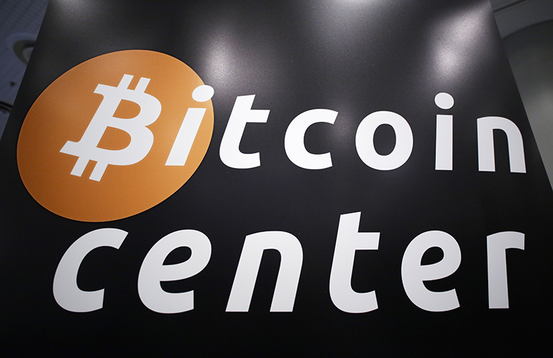A sign for the Bitcoin Center New York City, located in the city's financial district, is displayed at the Inside Bitcoins conference and trade show, April 7, 2014 in New York. The Associated Press