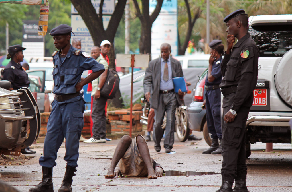 Guinea police secure the area around a man who collapsed in a puddle of water on the street, and people would not approach him as they fear he may be suffering from the Ebola virus in the city of Conakry, Guinea, on Wednesday. The man lay in the street for several hours before being taken to an Ebola control center for assessment.