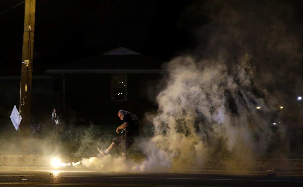 A protester kicks a smoke grenade deployed by police back in the direction of police wednesday in Ferguson, Mo.