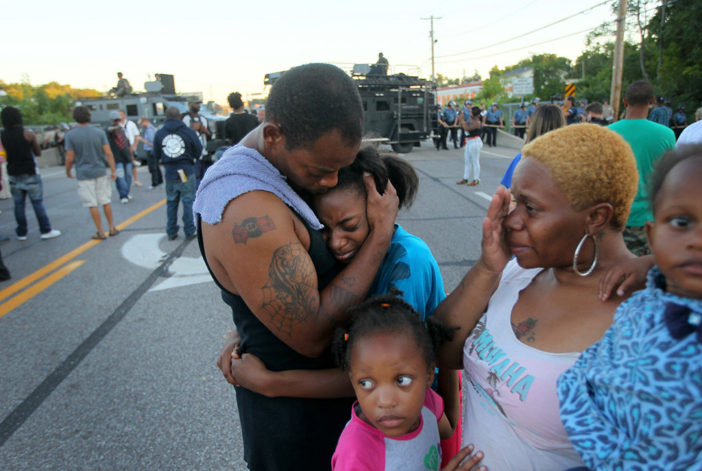 "Terrell Williams El hugs his daughter Sharell, 9, while standing with his wife, Shamika Williams, and daughters Tamika, 6, and Sharell, 2, on Wednesday in Ferguson, Mo. They were overcome with emotion after Williams El confronted police. ""I'm out here to stand for my children and their future,"" said Williams El."