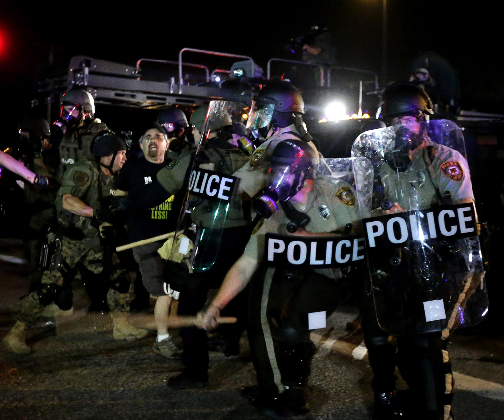 A man is detained after a standoff between protesters and police Monday night during a protest for Michael Brown, who was killed by a police officer Aug. 9 in Ferguson, Mo. Brown's shooting has sparked more than a week of protests, riots and looting in the St. Louis suburb.