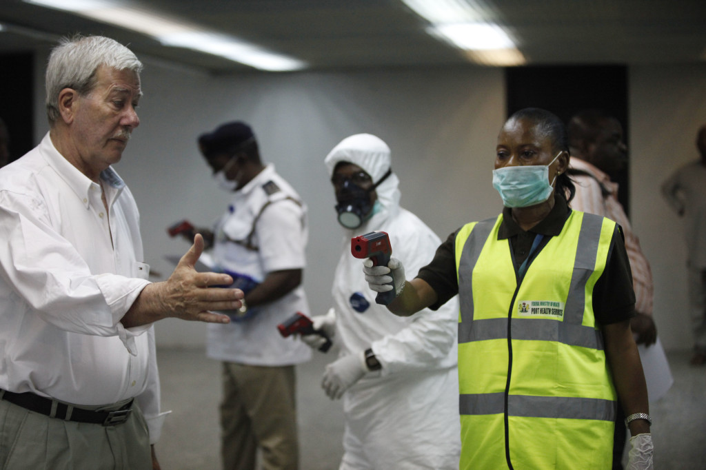 A Nigerian port health official uses a thermometer on a worker at the arrivals hall of Murtala Muhammed International Airport in Lagos, Nigeria, on Wednesday.