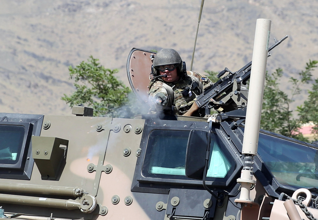 A NATO soldier opens fire in an apparent warning shot in the vicinity of journalists near the main gate of Camp Qargha, west of Kabul, Afghanistan, Tuesday. The Associated Press