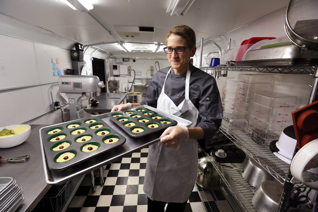 chef Alex Tretter carries a tray of cannabis-infused peanut butter and jelly cups to the oven for baking at Sweet Grass Kitchen, a well-established Denver-based gourmet marijuana edibles bakery which sells its confections to retail outlets throughout the state. Colorado marijuana regulators have drafted an emergency rule aimed at making it easier for new marijuana users to tell how much pot they are eating. The Associated Press