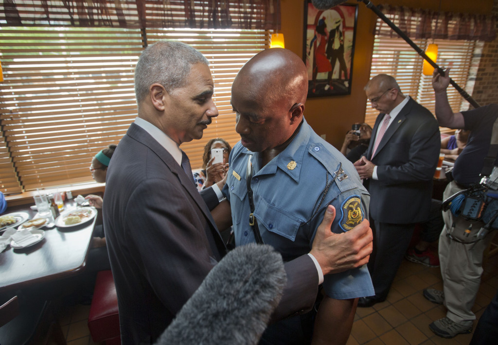 Attorney General Eric Holder greets Capt. Ron Johnson of the Missouri State Highway Patrol at Drake's Place Restaurant in Ferguson, Mo., on Wednesday.