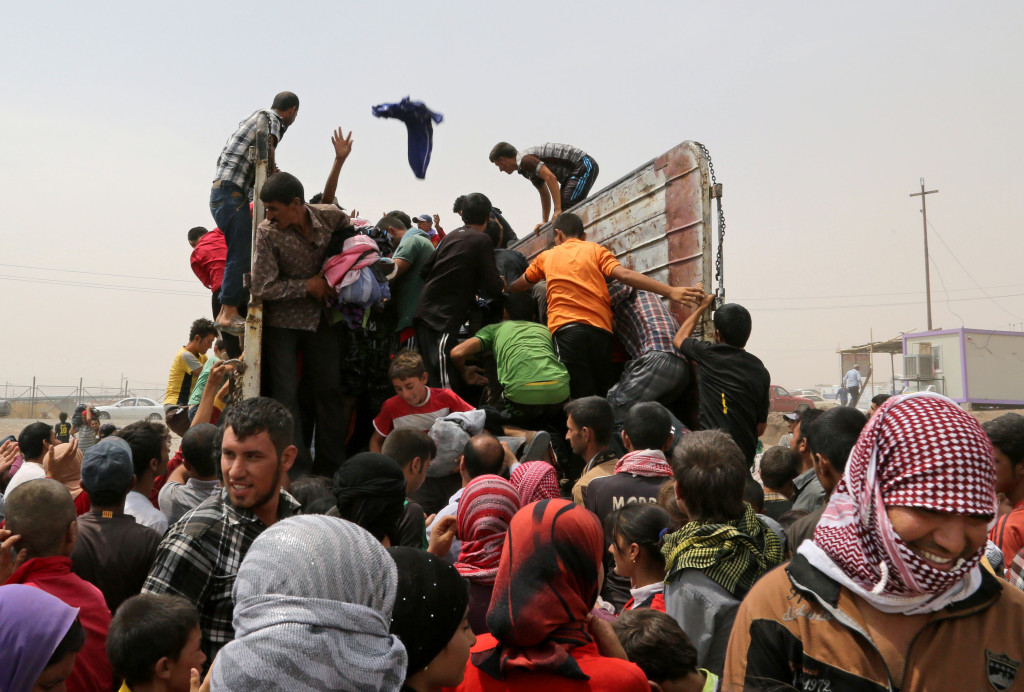 Displaced Iraqis gather to receive clothes provided by a charity at a camp  in Feeshkhabour, Iraq, on Tuesday. Some 1.5 million people have been displaced by fighting in Iraq since the Islamic State's rapid advance began in June, and thousands more have died. The Associated Press