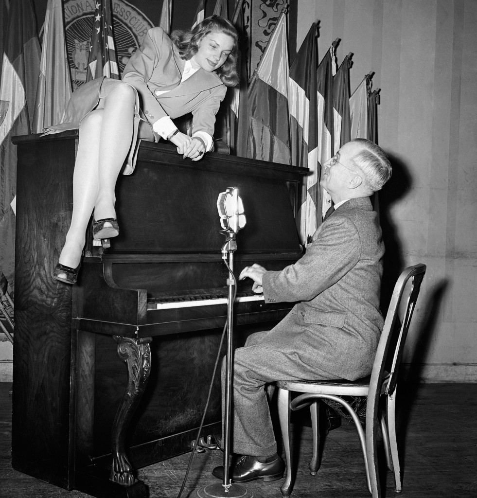 Vice President Harry S. Truman plays the piano as Lauren Bacall lies on during her appearance at the National Press Club canteen in Washington on Feb. 10, 1945.