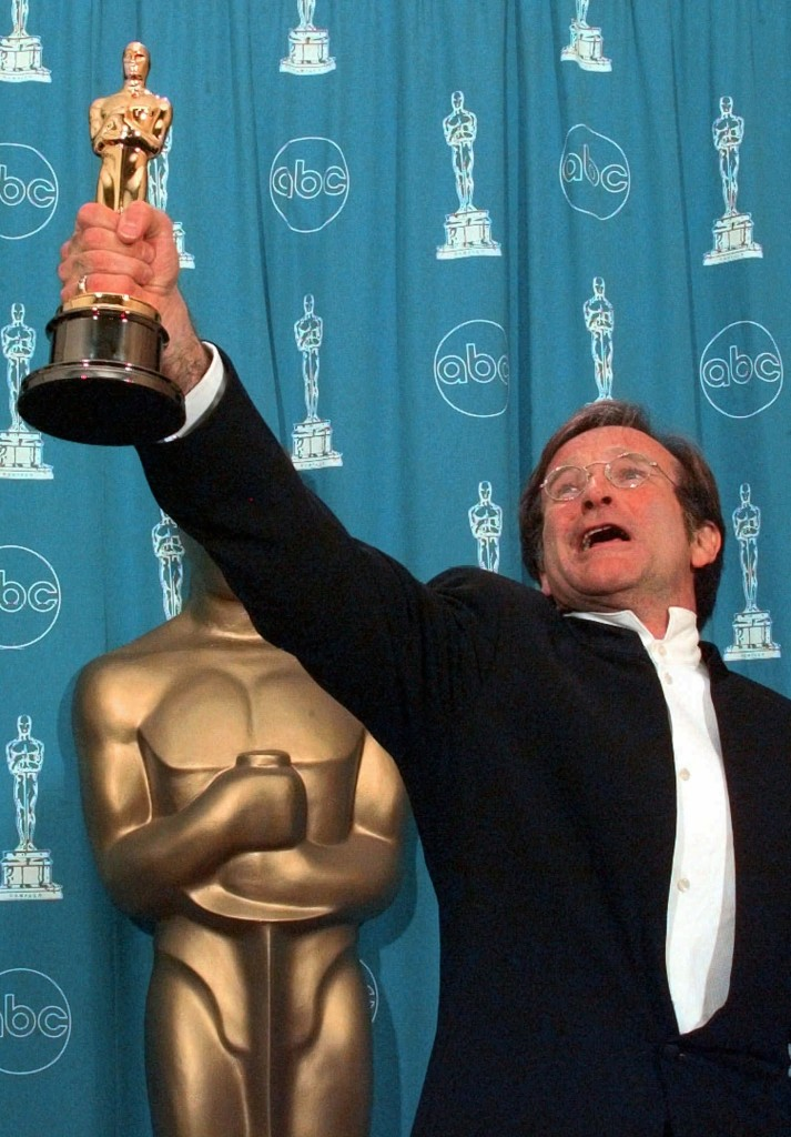 "Robin Williams, holding his Oscar high backstage at the 1998 Academy Awards after winning Best Supporting Actor for ""Good Will Hunting."""