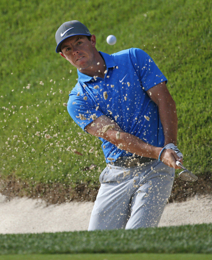 Rory McIlroy blasts out of a bunker on the 14th hole, setting up a par. McIlroy birdied three of the last four holes to move to 13 under, one shot ahead of Bernd Wiesberger. The Associated Press
