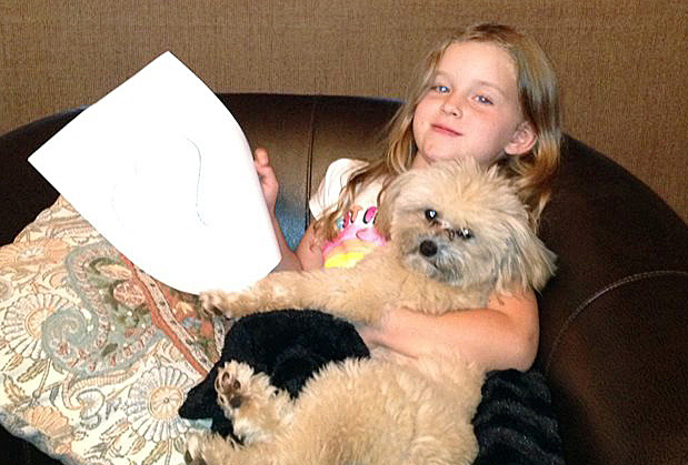 Coral Grimmett, 5, relaxes with her dog Harry at their home in Edmund, Okla., im in this photo provided by  Danel Grimmett. The Associated Press