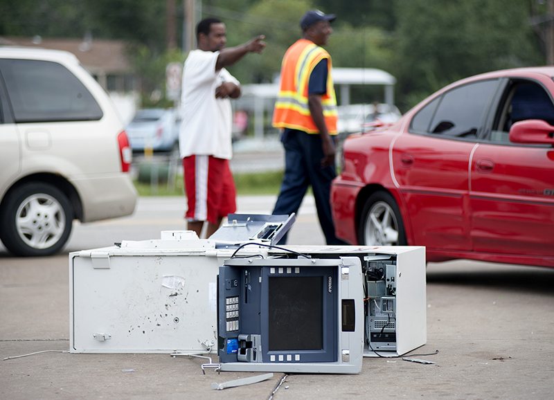Passers-by take a closer look Monday, at the ATM removed and opened at the burned-out QT gas station torched during the violence that erupted overnight in Ferguson, Mo., following a candle-light memorial for 18-year-old shooting victim Michael Brown. The Associated Press