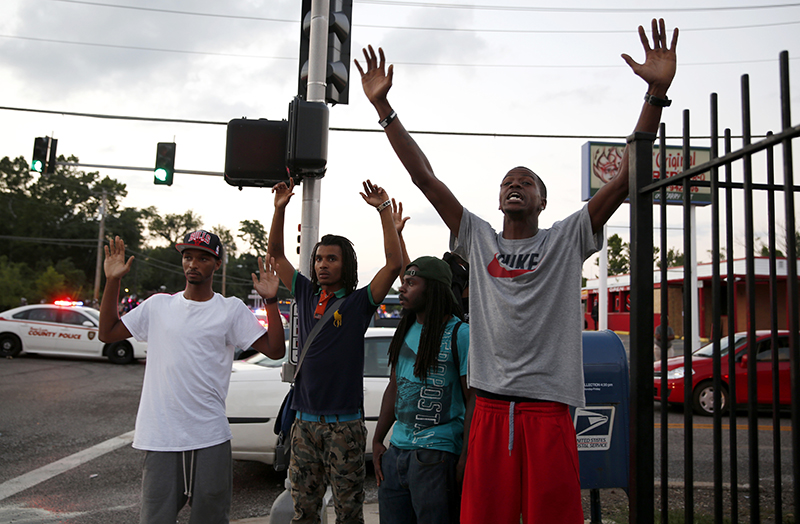 Protesters yell at police Monday, in Ferguson, Mo. The FBI opened an investigation Monday into the death of 18-year-old Michael Brown, who police said was shot multiple times Saturday after being confronted by an officer in Ferguson. The Associated Press
