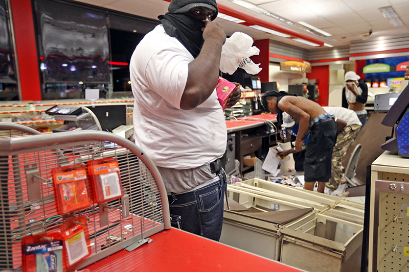 People are seen in a store Sunday, in Ferguson, Mo. A few thousand people crammed a suburban St. Louis street Sunday night at a vigil for unarmed 18-year-old Michael Brown shot and killed by a police officer. The Associated Press