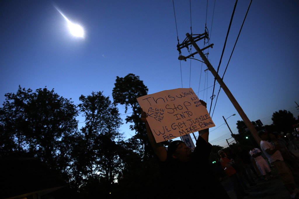 A protester holds up a sign as a police helicopter circles overhead Wednesday.