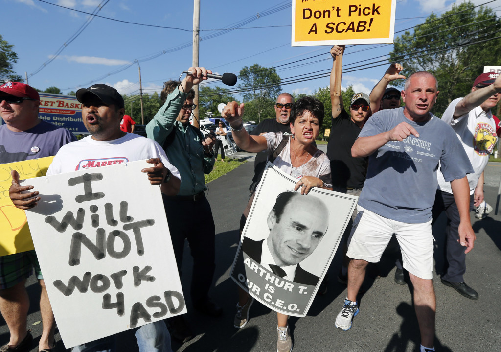 Protesters hold signs and taunt a car leaving the site of a Market Basket Supermarket job fair in Andover, Mass., on Aug. 6.
