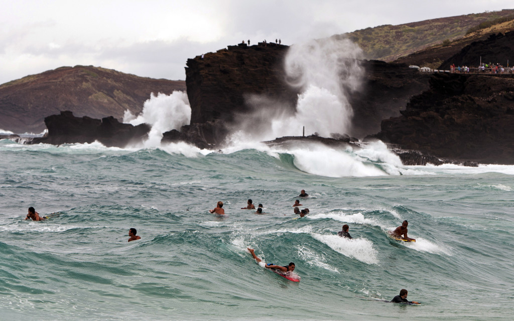 Surfers and body boarders wait for waves at Sandy Beach Park in Honolulu on Friday. Tropical Storm Iselle caused higher-than-normal waves in parts of the island of Oahu. The Associated Press
