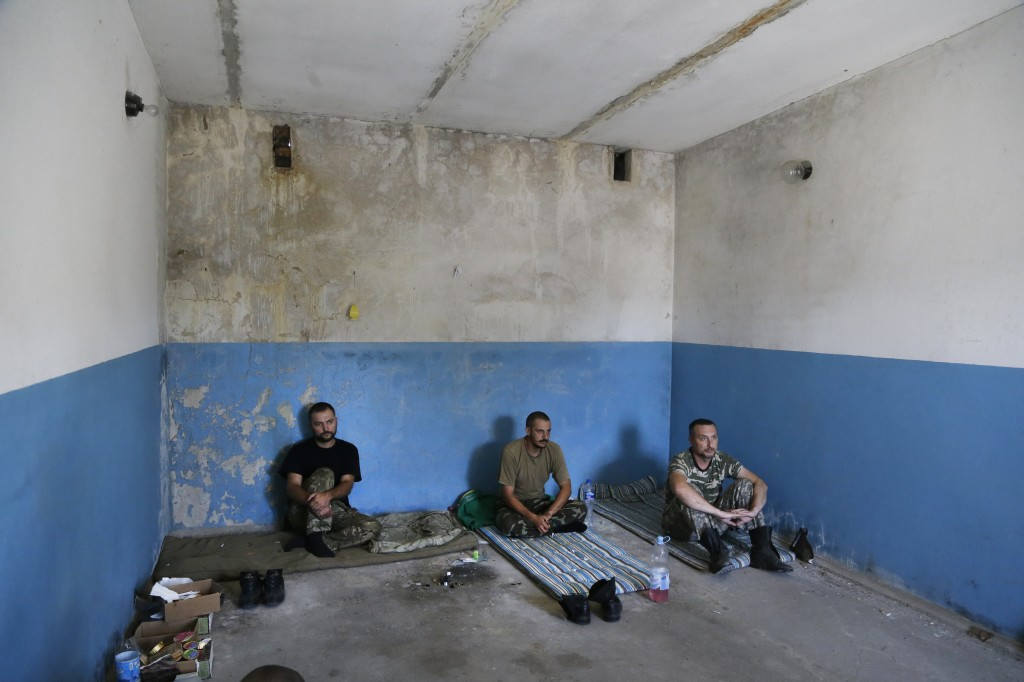 Captured Ukrainian border guards sit in a garage at the Novoazovsk border crossing point, in eastern Ukraine Friday. Novoazovsk fell swiftly to the rebels Wednesday after being pounded by shelling. The Associated Press