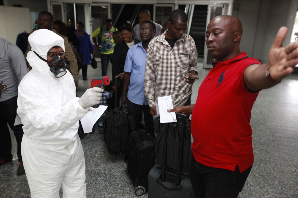A Nigerian port health official uses a thermometer on a passenger at the arrivals hall of Murtala Muhammed International Airport in Lagos, Nigeria,  Wednesday. The Associated Press