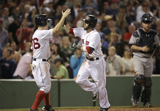 Red Sox second baseman Dustin Pedroia is welcomed home by Brock Holt after hitting a two-run home run in the second inning against the Yankees on Sunday. The Associated Press