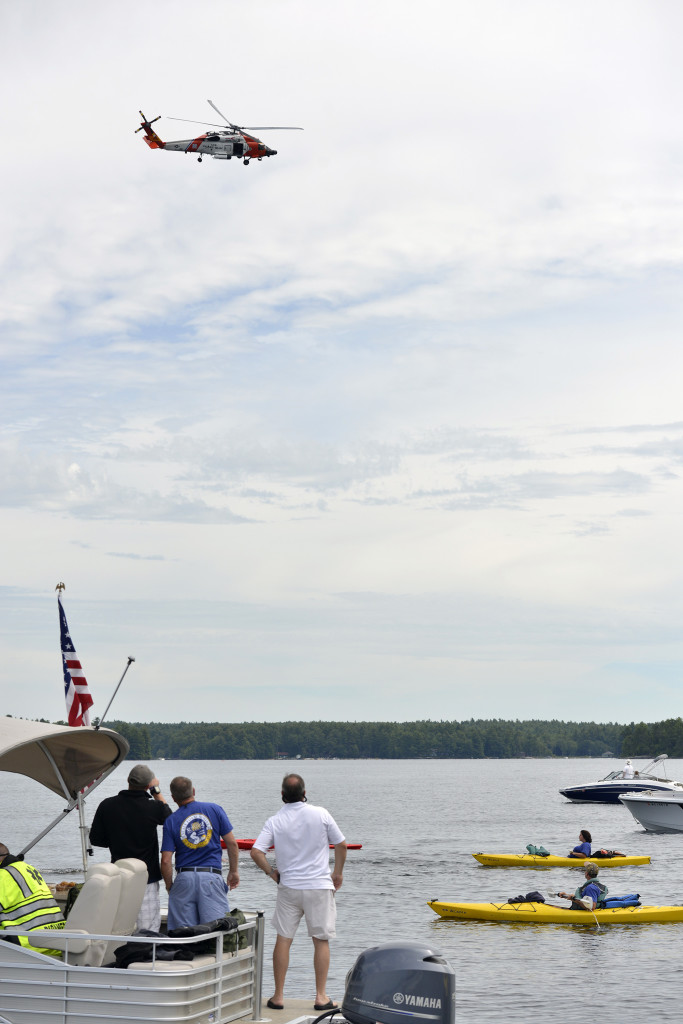 A United States Coast Guard helicopter from Cape Cod flies over Sebago Lake in Standish as four Navy SEALs swim 13.5 miles to raise money for Camp Sunshine in Casco on Thursday.