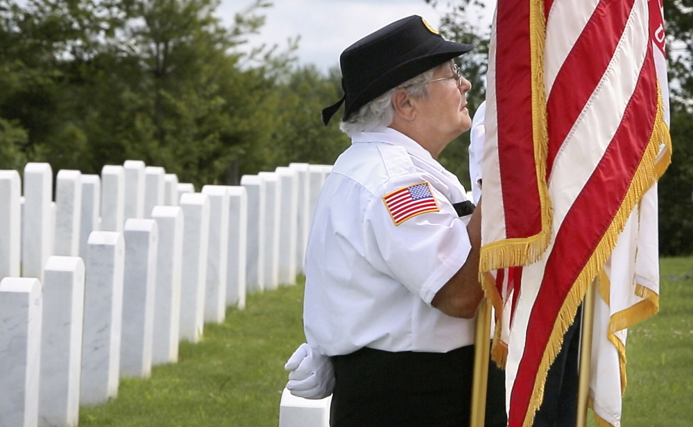 Elaine Brochu of Windsor holds a U.S. flag during a funeral at the Maine Veterans' Memorial Cemetery in Augusta. Brochu is a member of the Kennebec County Veterans Honor Guard, a volunteer group of veterans who, since 2003, have attended over 1,000 funerals of veterans in Maine.