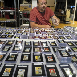Troy Thibodeau of Saco River Auction Co. examines a collection of more than 1,400 baseball cards from 1909, 1910, and 1911 in Biddeford. The collection will be auctioned off starting in January 2015.