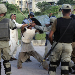 Police beat a protester during clashes in Islamabad, Pakistan on Monday. The violence comes as part of the mass demonstrations led by Muslim cleric Tahir-ul-Qadri and opposition politician Imran Khan that demand Prime Minister Nawaz Sharif resign.