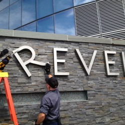 Revel employees Joe Lucchetti, left, and Robert Fitting remove letters from a sign at Revel hotel-casino in Atlantic City. The hotel closed Monday and the casino will close on Tuesday. Photo by Michael Ein/The Associated Press