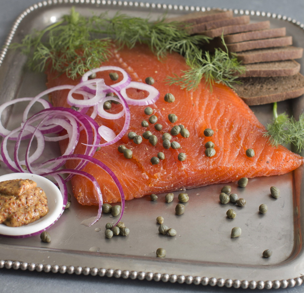 Gravlax is made by dry-curing fillets of salmon in a blend of sugar, kosher salt, fresh dill and a variety of other seasonings.