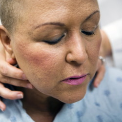 A radiation oncologist checks breast cancer Lourdes Suggs for neck lumps in Houston.