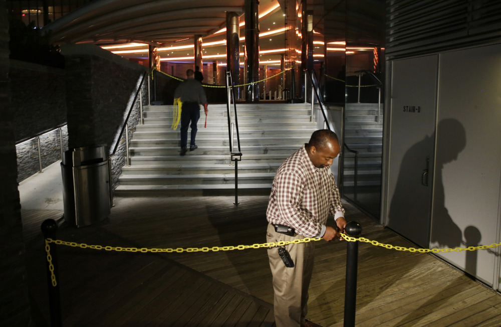A casino worker secures a chain across The Boardwalk entrance to the Revel Hotel Casino early Tuesday in Atlantic City, N.J. The casino was supposed to enliven the gambling market but is a $2.4 billion boondoggle.