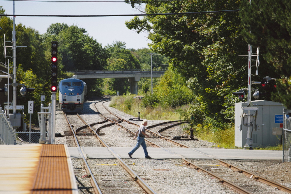 William Capistran crosses the tracks near the Brunswick train station last week. The LePage administration has taken an unusually active role in the controversy over a proposed Amtrak maintenance facility in a residential neighborhood of Brunswick.