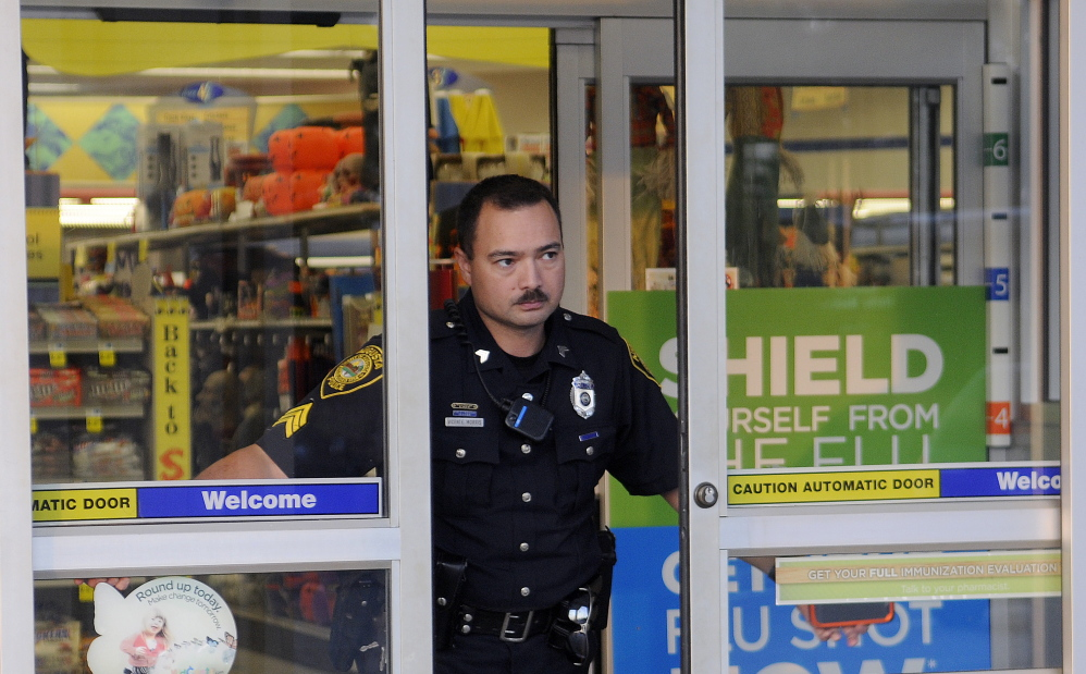 Augusta police Sgt. Vincente Morris closes the doors Tuesday at the Rite Aid pharmacy on Hospital Street in Augusta after it was robbed. Police were investigating a report of an attempted robbery at the Rite Aid on North Belfast Avenue in Augusta when the Hospital Street pharmacy was hit, according to police.