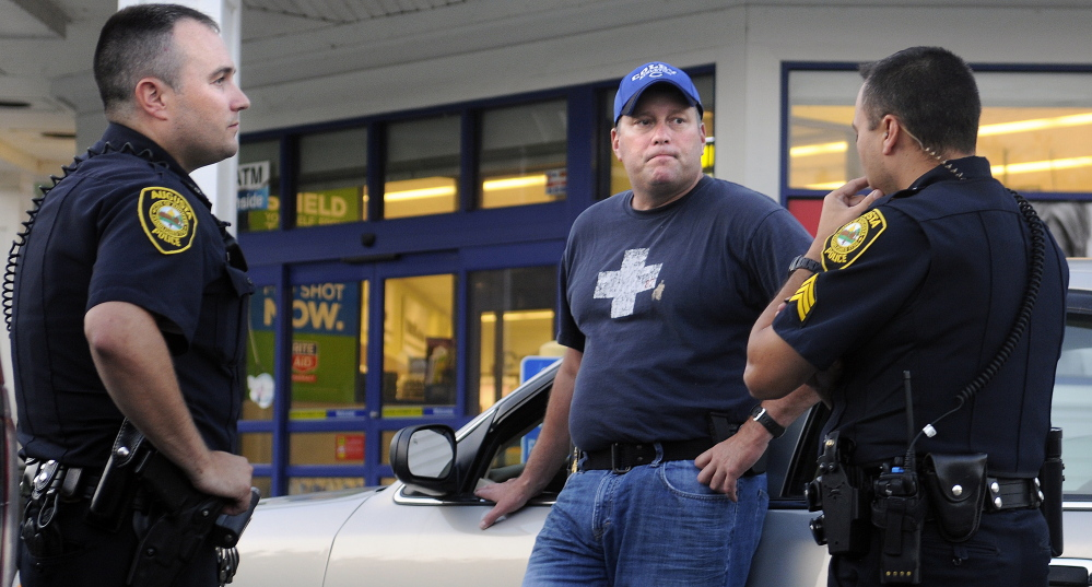 Augusta police Sgt. Vincente Morris, right, speaks with Augusta police Lt. Chris Massey, center, and Officer Jess Brann on Tuesday outside the Rite Aid on North Belfast Avenue in Augusta. As police were investigating an attempted robbery at the pharmacy, the Rite Aid on Hospital Street in Augusta was robbed.