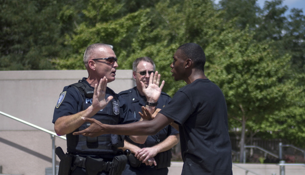 Police officers try to block an activist, demanding justice for Michael Brown, from advancing past the steps to the courthouse Aug. 26 in downtown St. Louis, Mo.