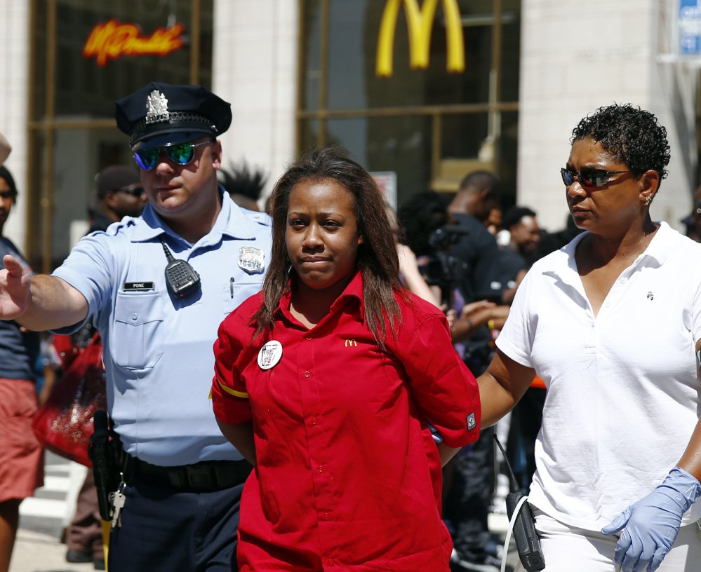 A fast-food worker is detained by police Thursday outside a McDonald's in Philadelphia during a protest to push fast-food chains to pay their employees at least $15 an hour.