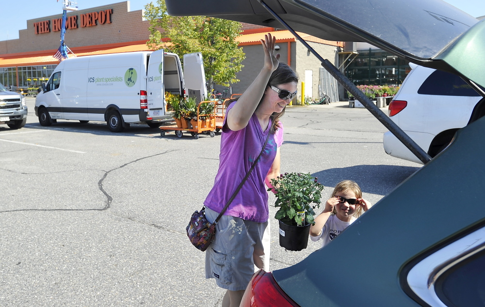 Sarah Sweeney of Portland puts the flowers she bought with her credit card into her car Friday. Gordon Chibroski/Staff Photographer