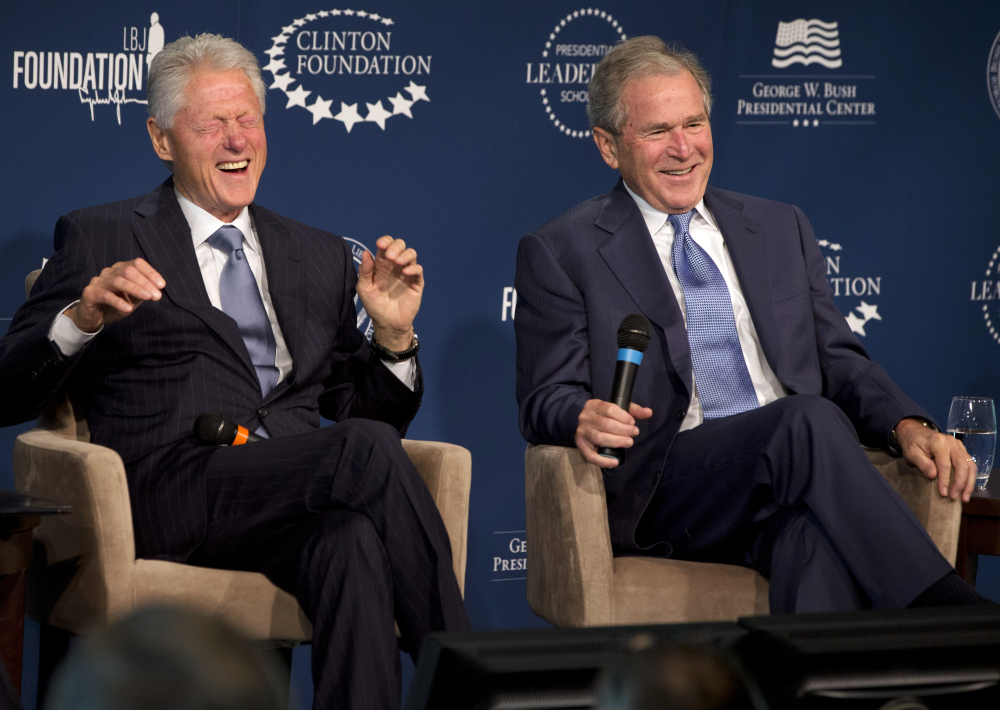 Former Presidents Bill Clinton, left, and George W. Bush trade stories at The Newseum in Washington as they launched a program to teach people about presidential leadership.