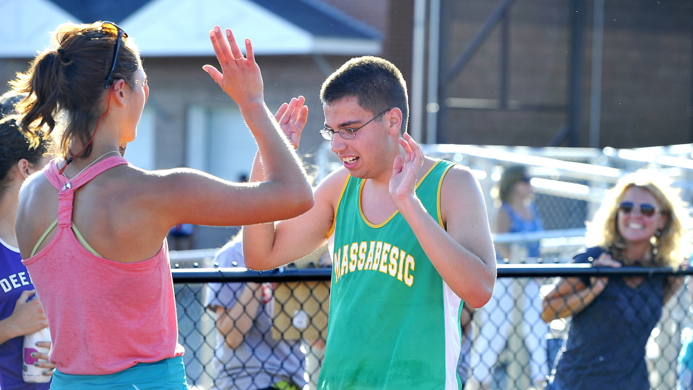 Massabesic junior Noah Harfoush, left, is greeted by assistant coach Sam Person after finishing the SMAA Relays at Thornton Academy last week. Harfoush, who is autistic, is one of three special needs runners on the Mustangs this season.