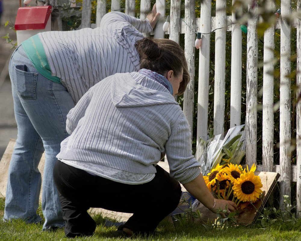 Two women lay flowers Tuesday outside the home of James Laurita. Many residents in the close-knit community of about 1,500 found it difficult to talk about his death.
