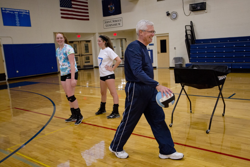 Yarmouth volleyball players Heather Clark and Makenzie Sheehan look toward coach Jim Senecal, at right, during practice Monday. The Clippers hope to repeat as Class B champions.   Gabe Souza/Staff Photographer