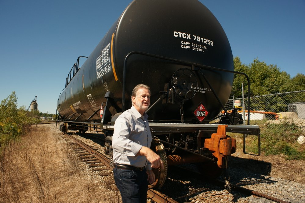 John Giles, president and CEO of the Central Maine & Quebec Railway, walks behind a tank car carrying propane as he inspects work in Hermon. Giles wants to modernize the railroad so it can operate efficiently, carrying lumber and other forest products as its primary cargo.