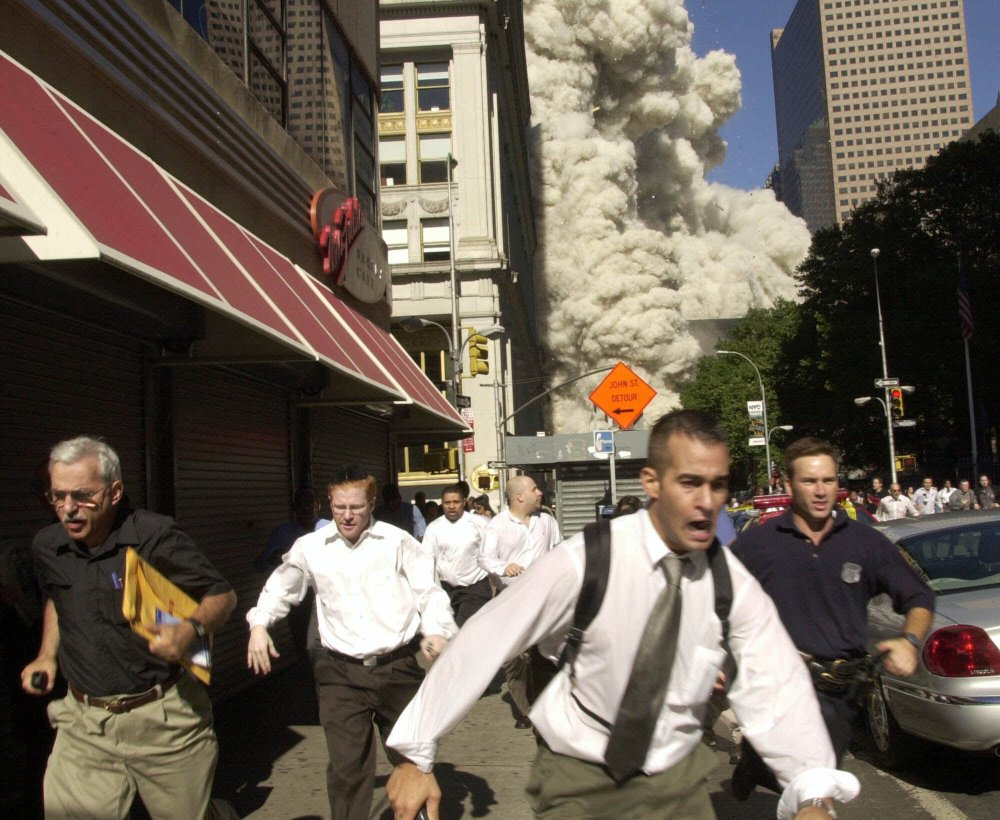People run as the World Trade Center collapses in New York on Sept. 11, 2001. More than a decade later, America and its allies prepare for conflict with Islamic militants.