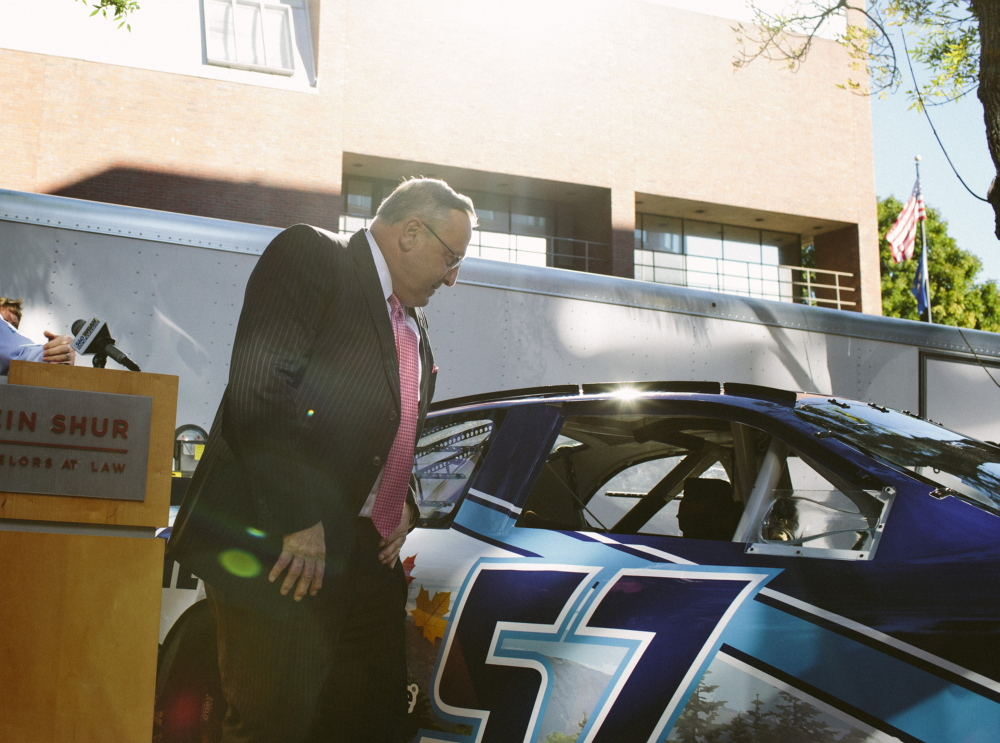 Gov. Paul LePage examines the model of NASCAR driver Austin Theriault's stock car in Portland on Friday. The