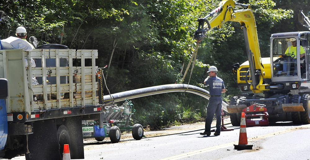 CUMBERLAND, ME - SEPTEMBER 10: A Cianbro crew removes the 8' pipe from the fusing machine after it cured as they prepare the pipe for burial along Route 88 in Cumberland Foreside.